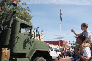 Daniel Schneider sets atop his dad's, Marvin Schneider, shoulders while giving a thumbs up to the military convoy that passed through downtown during the Old Time Saturday festivities. See page 8A for more photos.