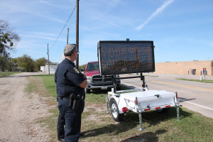 Police Chief Mike Sullivan sets up the newly acquired speed trailer on McKinney Street.