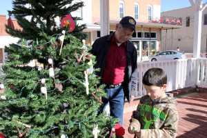 Farmersville Main Street volunteer Bill Daniel helps Tatum Elementary School student Colton Conallis pick out the perfect location on the downtown tree to hang his handmade ornament.