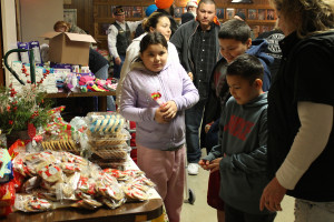 The Santillamo family of Blue Ridge, which lost their home and sustained injuries in the Dec. 26 tornado, check out a table full of treats at the Do-Over Christmas event hosted at Farmersville VFW Post 7426. Pictured in front are Hayti, Junior and Michael, with Mom and Dad, Zuleyma and Jose, behind.