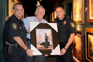 Police Chief Mike Sullivan, left, and Lt. Brian Alford accept a piece of art from Roy Blevins.