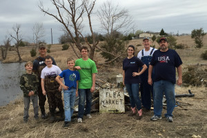 Volunteers clean up debris from ponds at LeAnn and Charlie Peters land after the Dec. 26 tornadoes.