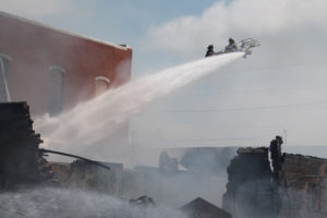The Farmersville Fire Department uses the aerial ladder on the Quint truck to help save the Clay Potter Auction House.