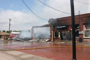 Firefighters battle a blaze downtown on May 28 for hours to save buildings. Two structures are a complete loss and one more suffered water and smoke damage.