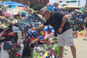 Lieutenant Brian Alford places a Farmersville PD patch on a memorial in front of Dallas Police headquarters over the weekend after an ambush in downtown Dallas July 7 that killed five officers.