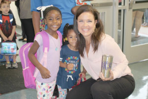Principal Ginger Ketcher greets head start student Skyylar Jones and her sister on the first day of school.