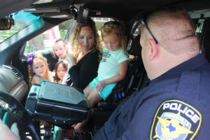 Harper Dyer, with Detective John Williams, looks curiously at a button inside a patrol car that turns on the siren. Though Harper wasn't too sure about the police officer, by the end of the Aug. 3 Summer Reading Club at Rike Library, she and the detective were good friends