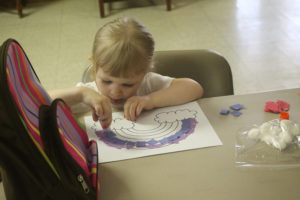 Megan Kruse, 3, puts together a rainbow at the imagination themed Summer Reading Club July 27 at the Rike Library.