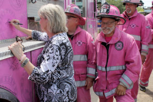 Tatum Elementary School Computer Lab Instructional Manager Marti Mason signs a pink firetruck as part of Pink Heals as a 10-year cancer survivor.