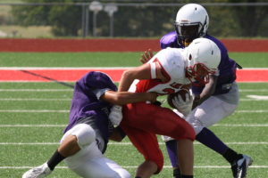 Farmersville defenders look to bring down a Lone Oak pass catcher that picked up a large chunk of yards during the Aug. 13 season opening scrimmage at Greenville's Cotten Ford Stadium. Pottsboro comes to town 7 p.m. Thursday for one final warmup.