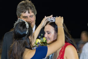 Homecoming Queen Anna Nibbelin smiles while being crowned by last year's Homecoming Queen Claudia Patino. Anna was escorted by her dad, David Nibbelin.