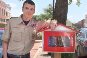 Eagle Scout Austin Miller stands with his little free library project downtown. The library will be dedicated Saturday, Oct. 15 at 2:15 p.m.